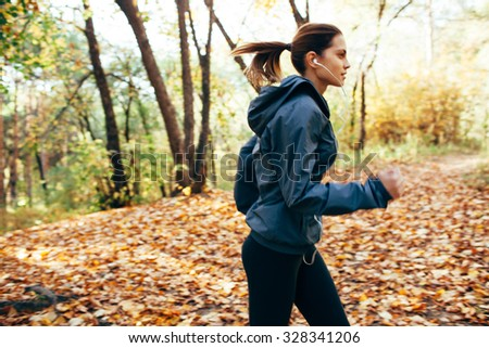 runner caucasian woman jogging in autumn park. Motion blur effect