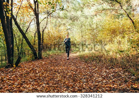 runner caucasian woman wearing dark gray jacket jogging in autumn park, overall plan - stock photo