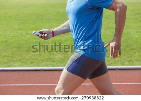 Runner checks his fitness data on a smartphone while running before uploading it to the cloud. He wears a fitness tracker wristband on the right arm. Unfiltered version - stock photo