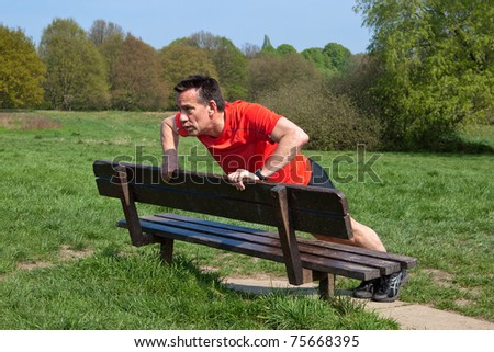 Runner doing pressups on a Park Bench - stock photo