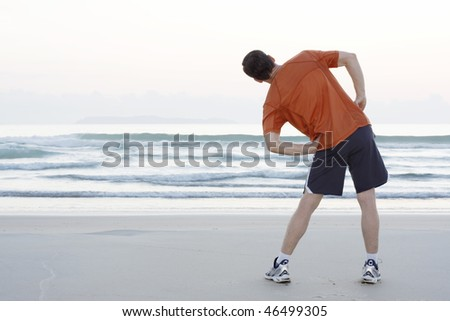 Runner doing stretching exercises on a beach early in the morning - stock photo