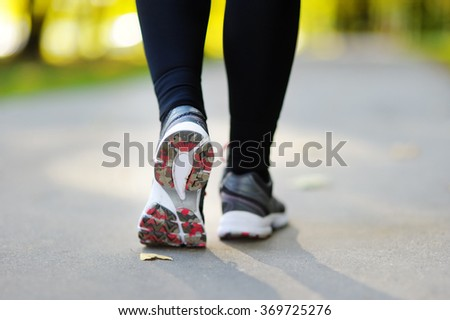 Runner feet running on road closeup on shoe. Woman fitness jog workout, wellness concept