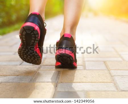 Runner feet running on road closeup on shoes. Woman fitness sunrise jog workout welness concept  - stock photo