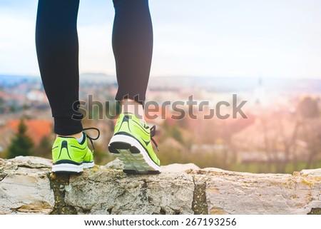 Runner feet running on the top of a hill closeup on shoe. woman fitness sunrise jog workout wellness concept. - stock photo