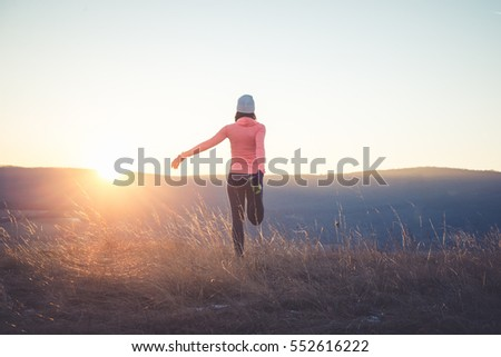 Runner girl stretching on top of the hill