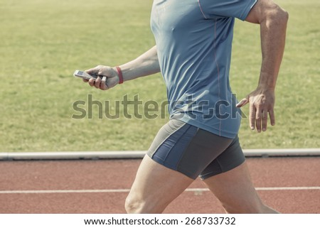 Runner in a stadium checks his fitness results on a smartphone while running. He wears a fitness tracker wristband on the right arm. Photo is filtered with slight antique effect. - stock photo