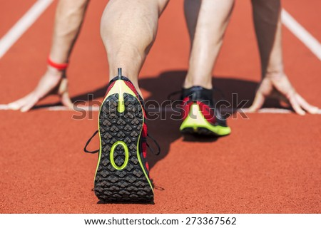 Runner in a stadium in start position with hands on the line. Unfiltered version. - stock photo