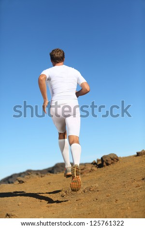 Runner in nature running away in back view. Fit fitness athlete model trail running wearing compression clothes, shorts, socks etc. - stock photo