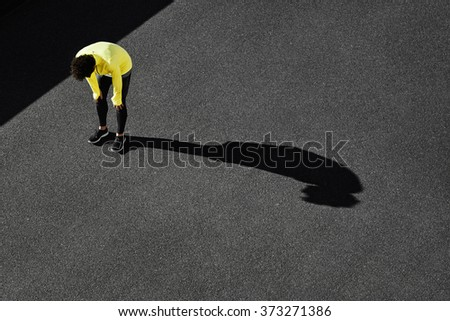 Runner in yellow sportswear resting after running. Jogging man taking a break during training outdoors in on black road on top view. Young Caucasian male fitness model after work out. - stock photo