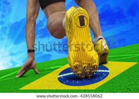 Runner is ready to start on tartan surface with brazilian banner. - stock photo