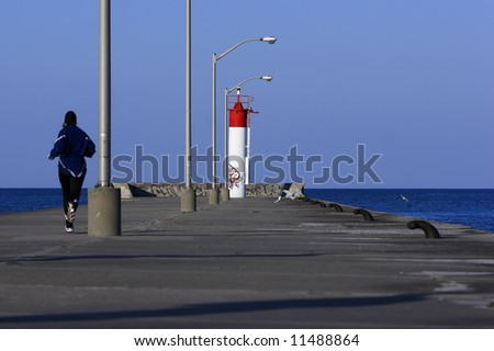 Runner jogging to the end of a concrete pier. - stock photo