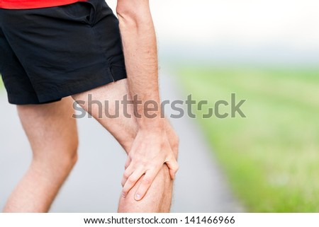 Runner leg and muscle pain during running training outdoors in summer nature. Health and fitness concept - stock photo