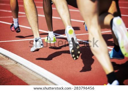 Runner legs in a stadium. Focus is on runner with dark skin. - stock photo