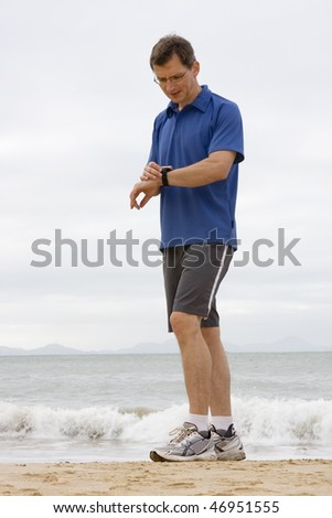 Runner looking at stop watch on a beach - stock photo