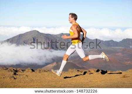 Runner man athlete running sprinting fast. Male sport fitness model training a sprint in amazing nature landscape outdoors at speed wearing sporty runners clothing compression socks. Strong fit man - stock photo