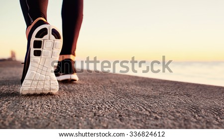 Runner man feet running on road closeup on shoe. Male fitness athlete jogger workout in wellness concept at sunrise. Sports healthy lifestyle concept  - stock photo