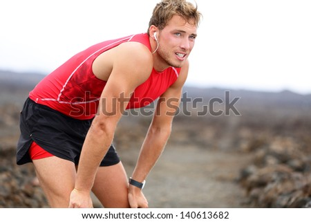 Runner man resting with music after running training for triathlon ironman on Hawaii. Male fitness model and triathlete relaxing looking with earphones listening to music. From Big Island, Hawaii, USA - stock photo