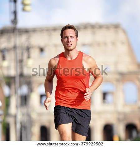 Runner man running at italian city Rome marathon near Colosseum, Roma, Italy. Handsome male athlete training cardio jogging on street with famous touristic attraction landmark in the background.