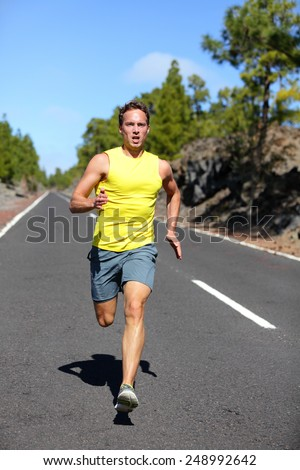Runner man running sprinting for success on run. Male athlete runner training at fast speed. Muscular fit sport model sprinter exercising sprint on forest road. Full body length of Caucasian model. - stock photo