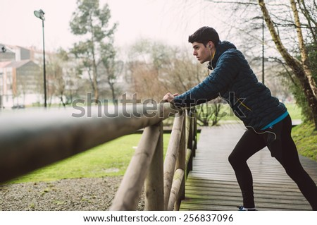 Runner man stretching in a park outdoors in a rainy day - stock photo