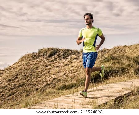 Runner man training on the beach - stock photo