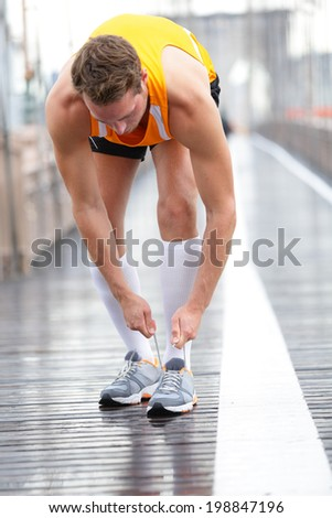 Runner man tying laces on running shoes, New York City on Brooklyn Bridge. Male athlete runner and feet closeup. Fitness model wearing compression socks. - stock photo
