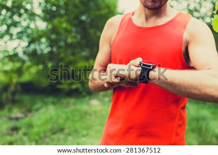 Runner on mountain trail checking looking at sportwatch smart watch, cross country runner checking performance, GPS position or heart rate pulse. Sport smartwatch and fitness equipment on summer trail - stock photo
