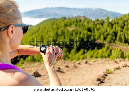 Runner on mountain trail looking at sportwatch, checking performance or heart pulse trace, heart monitor. Cross country running in beautiful nature, Canary Islands. - stock photo