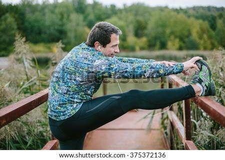Runner on rusty bridge stretching against green nature - stock photo