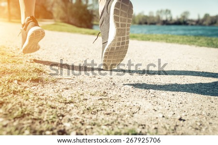 runner on the path. woman training in the park. focus on the ground and shadow. concept about sport and healthy lifestyle