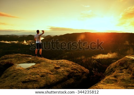 Runner on the peak. Man in his target gesture triumph with hands in the air. Crazy man in black pants and white sweaty t-shirt, - stock photo