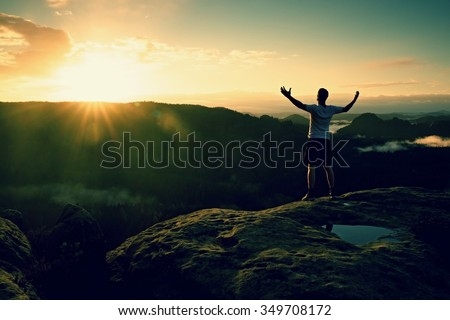 Runner on the peak. Man in his target gesture triumph with hands in the air. Crazy man in black pants and white t-shirt, - stock photo