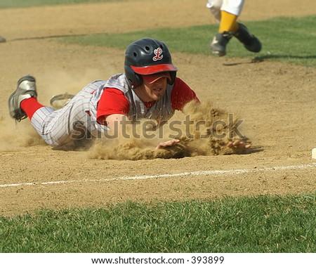 runner slides into third base - stock photo