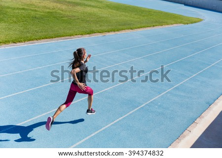 Runner sprinting towards success on run path running athletic track. Goal achievement concept. Female athlete sprinter doing a fast sprint for competition on blue lane at an outdoor field stadium. - stock photo