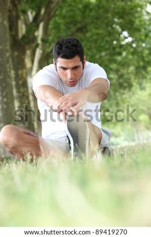 Runner stretching on grass - stock photo