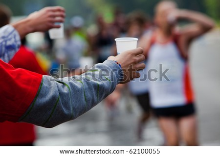 Runner take a water in a marathon race - stock photo