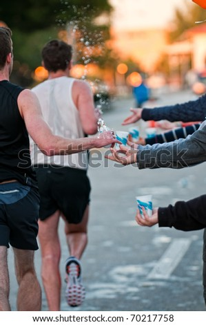 Runner takes water during a marathon race - stock photo