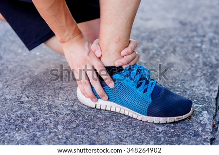 Runner touching painful twisted or broken ankle. Athlete runner training accident. Sport running ankle sprain.  - stock photo