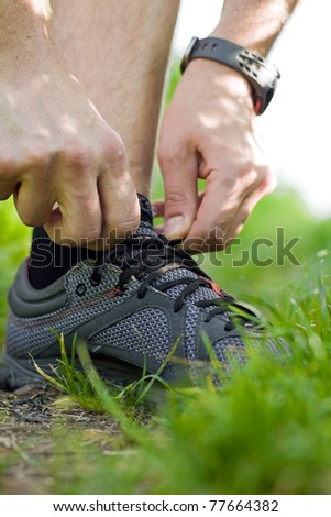 Runner tying sport shoe in green summer forest, exercise outdoors. Young male hiker ready to hike or walk and run. Motivation and inspiration fitness concept outside nature.
