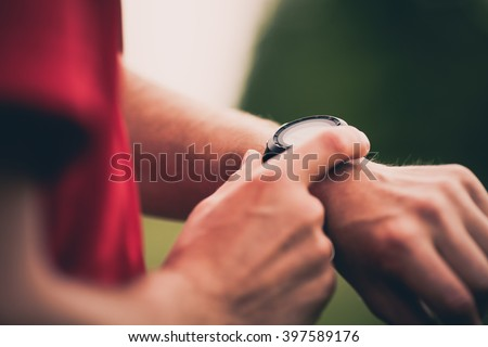 Runner using heart rate monitor training running, smartwatch checking performance or GPS. Man athlete looking at stopwatch. Healthy runner on running trail. Wearable technology for tracking activity. - stock photo