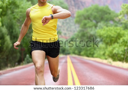 Runner with heart rate monitor sports smart watch. Man running looking at his pulse outside in nature on road with smartwatch. - stock photo