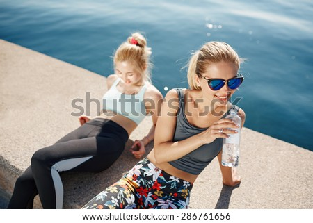Runner woman drinking water on beach with asian friend running in background. Happy smiling fitness sport model take a break after outdoor workout. - stock photo