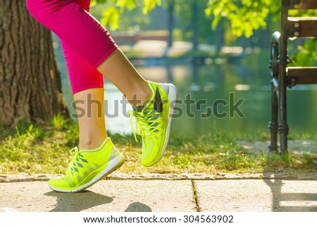 Runner woman feet running on road closeup on shoe. Female fitness model sunrise jog workout in the sunny park outdoors. Sports healthy lifestyle concept.