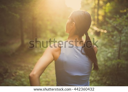 Runner woman jogging in the forest.Beautiful fit female fitness woman training and working out outside in summer as part of healthy lifestyle.Fitness woman running at sunset in woods - stock photo