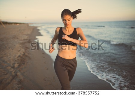 Runner woman jogging on beach in sports bra top.Beautiful fit female fitness woman training and working out outside in summer as part of healthy lifestyle.Fitness woman running at sunset on beach - stock photo