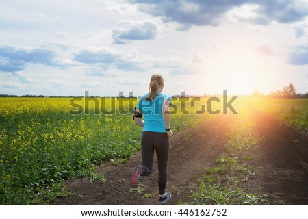 Runner woman running on road in beautiful nature. Jogging training for marathon.