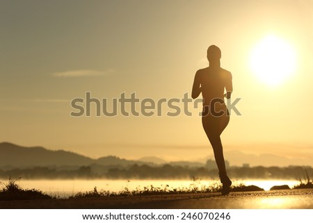 Runner woman silhouette running at sunset with the sun in the background - stock photo