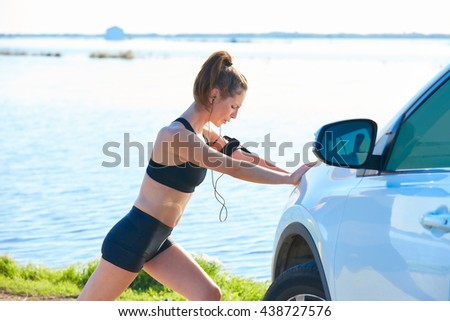 Runner woman stretching on a car in the lake outdoor