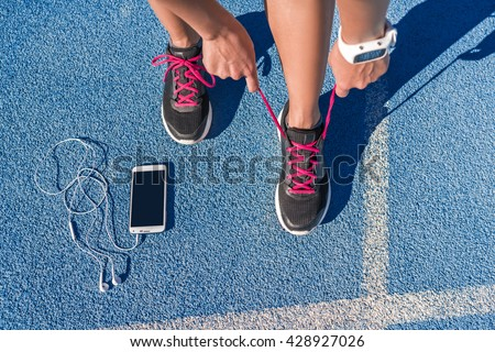 Runner woman tying running shoes laces getting ready for race on run track with smartphone and earphones for music listening on mobile phone. Athlete preparing for cardio training. Feet on ground. - stock photo