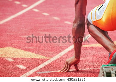 Runners fingers on the starting line, ready for the start of a track and field race - stock photo